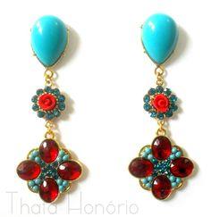 Cód: BD297 <br>Tam: 8,5 cm <br>Brinco em banho de ouro com pedras de resina azul turquesa, pedras acrílicas vermelhas, strass, bolinhas marroquinas e florzinha de biscuit.