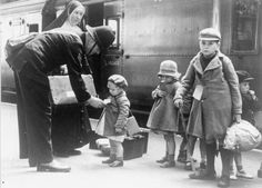 A policeman helps some young evacuees, and a nun who is escorting them, at a London station.