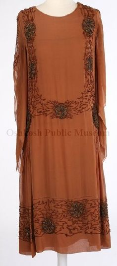 1920s rust-colored crepe dress; long sleeves with slashed-look 2-part opening; decorated down each side of front, back neckline 3/4 down top of sleeves, around hips, around bottom of skirt with seed beads of brown glass and iridescent bronze metal; extra shirred hip panels on each side also trimmed with beads.