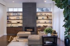 The fireplace is a strong vertical feature in gray stacked stone, and paired with the dark floating cabinets, grounds the wall. Floating shelves and transom windows add lightness.