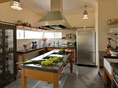 Any chef would be happy to call this kitchen home. The large industrial-style island features a heat-resistant concrete countertop and pro-style gas range with plenty of counter space to spare. An open wire rack below keeps pots and pans within easy reach. Photo courtesy of Place Architects. Photo by Aaron Britton