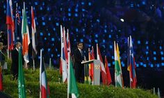 Sebastian Coe speaks during the London 2012 opening ceremony surrounded by all the flags of all the nations.