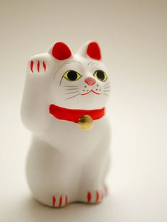Beckoning cat 招き猫 - In Japan, cats are considered to invite people and fortune into the homes, therefore Maneki-neko have one paw raised to beckon them inside.