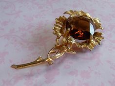 A very fine large goldtone metal fancy flower design vintage jewelry brooch set with a huge sparkly golden amber faceted glass stone. by vintagejewelleryetc on Etsy https://www.etsy.com/listing/220410175/a-very-fine-large-goldtone-metal-fancy