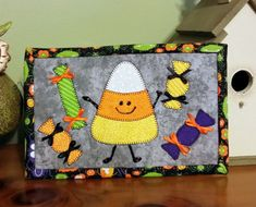 """PDF Pattern to make this Halloween themed mug rug or Candy Corn mini quilt. Made with these Halloween appliques. Measures 6 1/2"""" x 10""""  You can use them for setting your mug on with a snack, or my favorite way, leaning them against the wall in my hutch. You can even stitch rings to the back and hang on your wall.  These are the funnest of things to make! If you choose the machine applique, you can whip these up in no time. They make great gifts when given with a cute mug. They are so easy…"""