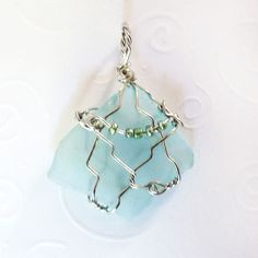 """Pretty translucent, light blue cultured sea glass wrapped in silver plated jewelry wire and accented with metallic aqua seed beads. 1.75"""" x 1.25"""" (4cm x 3cm) Your handmade sea glass pendant will arriv"""
