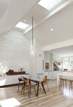"""Biała, rustykalna kuchnia z odsłoniętą cegłą pomalowaną na biało. Okna dachowe, zabudowa kuchni i niesamowita lampa. A do tego każde krzesło w jadalni inne i """"pływający"""" kredens. Jest eklektycznie, świetliście, przestronnie i niebanalnie. Jak Wam się podoba?  via: interiordesu"""