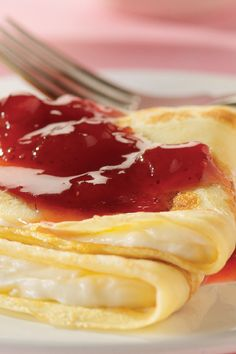 Cream Crêpes – In this elegant dessert or brunch dish, this recipe for homemade crêpes is spread with a lemony cream cheese, folded and served with a warm strawberry sauce.