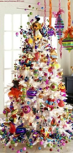 bright whimsical christmas tree decorated in fun non traditional colors this looks almost exactly like my tree that we have in our den