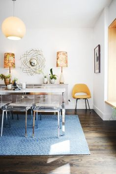 Beautiful dark wood flooring and a thick blue carpet is a perfect blend of being practical and comfy in a dining room space.