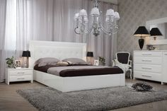tête de lit en cuir capitonné blanc neige, commode assortie, lustre Romeo, tapis shaggy gris taupe et parquet chevron