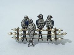 antique diamond, cabochon sapphire, pearl, silver, and gold bird brooch