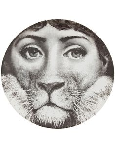 White porcelain plate from Fornasetti featuring a black and white 'lion woman' print.