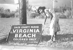 """1950: Woman By Virginia Beach Sign That Says """"Colored Only"""" Courtesy of State Library & Archives of Florida One reader stated: """"Virginia Key Beach was given to the """"Colored Only"""" because they thought the raw sewage was gonna flow to that beach. However the tides never took it that way."""""""