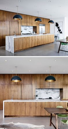 Polished concrete floors, white walls and ceiling give, walnut cabinets on the wall and on the island, Marble countertops and backsplash, pendant lighting above the island