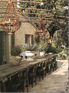 Roses and Rust. Cool unique outdoor dining area for parties... Wood table, with metal chairs and rusted chandeliers.