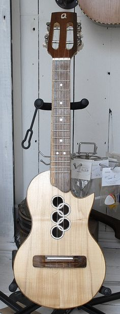 Quex Tenor Ukuele with 5 overlapping sound holes resembling Olympic rings. RESEARCH - cSw - http://www.pinterest.com/claxtonw/4-5-6-strings/ - QUEX builds musical instruments from local trees. But Mahogany trees don't grow in the UK / Britain. So when baulks (roughly squared timber beams) of solid mahogany were stripped out from a gallery being re-furbished in the Powell-Cotton Museum, the wood was obtained to make literal museum piece relatives of classical guitars:}