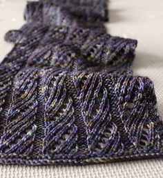 This lacy scarf consists of a twelve row lace pattern that is easy to learn and repeats throughout. It is worked in one skein of Malabrigo Arroyo and is light and airy with beautiful drape and softness. Pattern includes written and charted instructions.