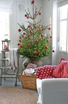 Simplicity: Natural pine tree in a large  natural fiber basket with red decorations / http://vibekedesign.blogspot.co.uk/2012/12/its-beginning-to-look-alot-like.html#