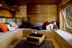 I like this tree house interior.  However, I might one of those tables you see on a boat where it lowers and becomes flush with the bed so that an additional bench mat could be placed upon it, transforming part of the bench into a big bed.
