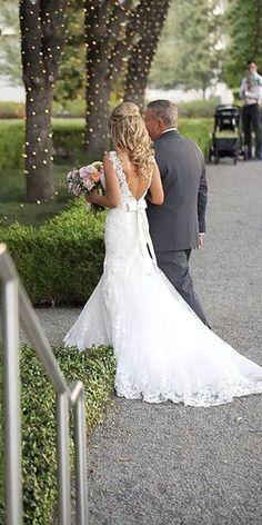Brautkleid aus Spitze mit Schleppe. Die Träger aus Spitze halten das fast rückenfreie Hochzeitskleid.
