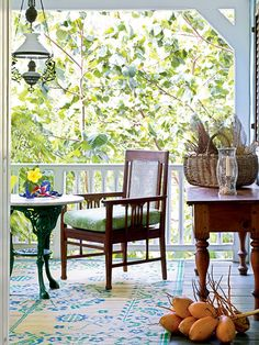 This cozy personal porch feels a part of nature with its combination of lush island vegetation and vibrant green accessories. A whimsical ceiling fixture, emerald green marble-topped table, and a patterned rug play off the natural beauty.