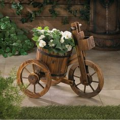 This may be the most charming plant holder ever! The rain barrel potted plant holder features authentic black metal banding and is set on a wooden tricycle frame. From the wagon wheels to the little b