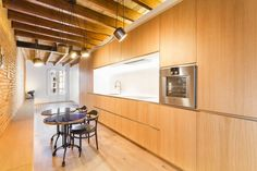 Size made natural oak panel kitchen from a refurbished apartment in Enric Granados, Barcelona by Àmbit Arquitectes Size made in mass oak panel kitchen cabinets under and over a white countertop. All the equipment as fridge, dishwasher and extraction is integrated in the cabients.
