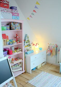 Love all the little colourful cases on top of the pink bookcase. Pretty room for a little girl