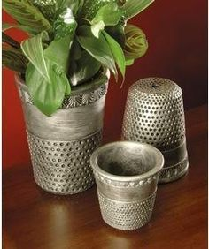 Pots by hand or wheel and incised to look like thimbles.  Stain with silver leaf and shoe polish.