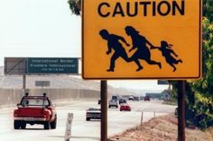 Caution sign depicting running illegal immigrants at a border crossing