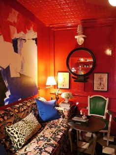 Nick Olsen's apartment.  Red lacquer walls.  Painted tin ceilings.  Chintz floral sofa.  Small NoLiTa Apartment in NYC.