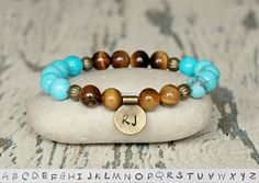 This personalized initial beaded bracelet created with gemstone tiger eye beads, blue howlite beads, metal spacers and metal charm with custom initial. Tigers Eye is a stone of protection that is also very stabilizing and grounding. It enhances integrity, willpower, self-confidence,