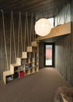 The stair doubles as a bookcase and has a guard made of heavy rope, which also guards the loft above.
