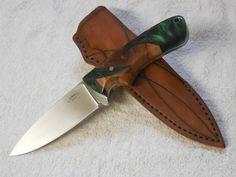 Acryl-Pflaumen-Jäger   Dieses Jagdmesser mit einer 10,9 cm langen Klinge aus Böhler N690 ist ingesamt 22,2 cm lang und im Griffbereich getapert (nach hinten verjüngt).  Die Griffschalen bestehen aus Pflaumenholz, das in grünes Acryl gegossen ist.  Ein ganz besonderer Augenschmaus und Handschmeichler.  Zu dem Messer gehört die von mir handgefertigte Lederscheide.