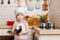 Kleines Mädchen in Schürze und Mütze des Kochs in der Küche steht in der Nähe von Herd im Haus. Mutter Helfer. 2 Jahre alt.