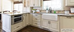 beautiful cream colored cabinets with farmhouse sink and under the counter microwave