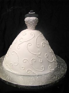 Bride Dress Cake - I made this cake  from a doll cake pan and covered it in fondant. I used a pattern press for the scrolls and I pipped the dots  on with  royal icing for the detail. I used a inexpensive doll pic for the body part which I covered with fondant. I made the necklace also from fondant.