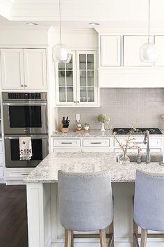 @carolineondesign White shaker cabinets and soft grey subway 3x6 tile backsplash. LG Viatera Quartz countertop in Everest. #whitekitchen #whiteshakercabinets #kitchendesign
