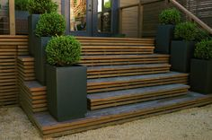 Charcoal planters on steps. Slats used for stairs and underhouse door. Charcoal doors. Front door