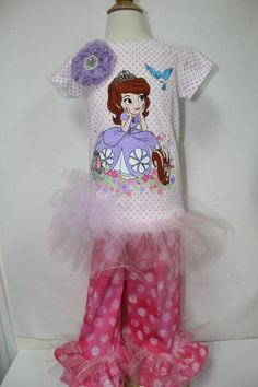 Your little princess will love wearing this precious outfit for any celebration. It is so pretty with the big tulle ruffles that go around the shirt and the bottom of the ruffled pants. The pants are hot pink polka dot with an elastic waist and ruffles on the bottom with flower detailed top stitching. The shirt has a large flower attached to the shoulder that includes faux pearls and rhinestones. The shirt also has a large lavender tulle bow at the drop waist. Your little princess will feel…