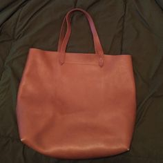 Madewell transport tote Used about 2-3 times. Interior shows no pen marks etc, but exterior does show two small pen marks as pictured. Never tried to remove it because I didn't want to ruin the bag lol. A little wear on the corner of the bag. Overall in excellent condition. Color is in English saddle. Madewell Bags Totes
