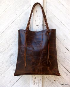 Distressed Brown Leather Tote by Stacy Leigh Heavily distressed, vintage looking , pull up leather, in a chocolate / chestnut brown color. Simple style bag with lots of character marks. Pull up leather lightens in color when scuffed or scratched. Open top with magnetic snap. Unlined, all leather bag. 2 drop in pockets. Double braided shoulder straps with 10 drops. Bag is 14 by 14. Each bag will be slightly different due to the uniqueness of the cowhides. **This bag may also be ordered fully…