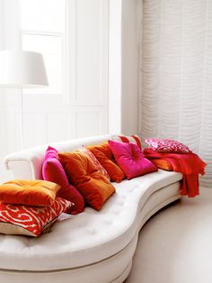 Love the stark white interior with a kidney-shaped sofa scattered with throw pillows in bright magenta and orange hues