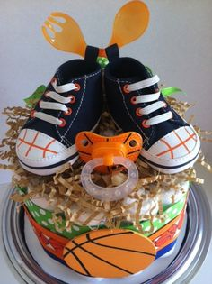 A very sporty orange, blue and green basketball mini diaper cake... perfect for a baby boy! This mini diaper cake makes a great shower gift or decoration/centerpiece. It also makes a stylish nursery decoration after the shower and is easily disassembled when baby is ready to use the diapers (and pacifier, utensils AND hi-tops!)    Single Tier Mini Diaper Cake includes:  - 15 size 1 Pampers Swaddlers disposable diapers  - wood basketball decorations (perfect for the babys scrapbook!) with…