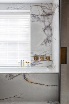A black and white marble bathroom with white Window Shadings and warm brass fixtures by Caballero Design
