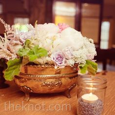 Antique containers filled with soft colored flowers complimented the subdued wedding colors.