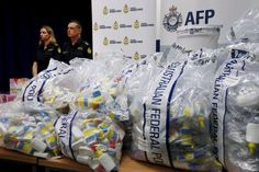 A quantity of liquid methamphetamine disguised in various packaging is put on display by Australian Border Force officers at the Australian Federal Police headquarters in Sydney
