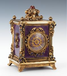 """Ornate gilt sterling silver and enameled carriage clock. Case set with semi-precious stones, purple guilloche enamels. Gilt and enameled face with Roman numerals, with Reuge music box. Red wool felt underneath. The music box plays the """"Blue Danube"""" waltz by Strauss."""