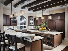 A kitchen featuring richly stained wood, glass-front and gridded cabinets, and simple hardware. The double-layered pendant lights add a bit of modern flair. Do you like? Source: https://www.zillow.com/digs/Home-Stratosphere-boards/Luxury-Kitchens/